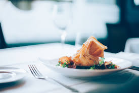 A steaming plate of food at a high end restaurant