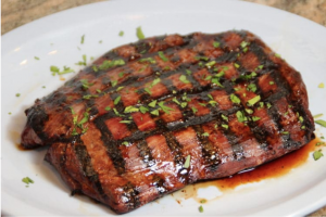 A perfectly seared steak seasoned with herbs