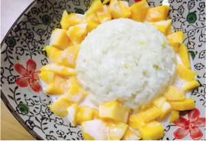 Cubed mango surrounding sticky rice with drizzled coconut milk