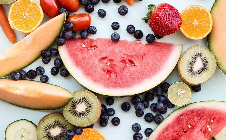 Fruits such as cantaloupe, watermelon, blueberries, kiwi, strawberries and tangerines scattered on a background. Fruits are naturally cooling foods that can help you stay cool.